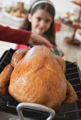 Woman holding turkey in roasting dish, girl in background