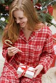 Woman holding candy cane and Christmas parcel