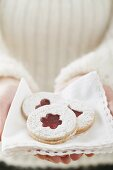 Woman holding jam biscuits on napkin