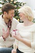 Woman giving man Christmas gift