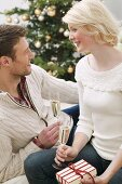Man & woman holding glasses of sparkling wine & Christmas gift