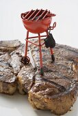 Grilled T-bone steak with toy barbecue