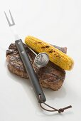 Beef steak with corn on the cob, carving fork & thermometer