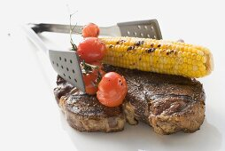 Grilled T-bone steak, corn on the cob, tomatoes, grill tongs