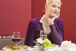 Woman with shrewd expression waiting for partner at table