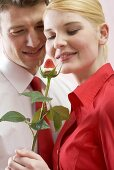 Romantic couple with chocolate-dipped strawberry on rose stalk