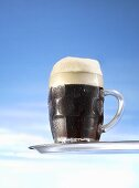 Dark beer in glass mug on tray