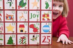 Kleines Mädchen guckt hinter Adventskalender hervor