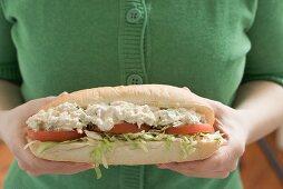Woman holding chicken salad sandwich