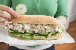 Woman holding tuna sandwich