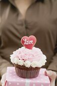 Woman holding cupcake and gift for Valentine's Day