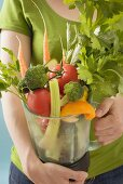 Woman holding fresh vegetables and herbs in liquidiser