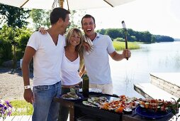 One woman and two men standing by barbecue