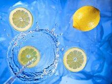 Stream of water running onto lemons and lemon slices
