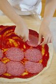 Girl putting slices of salami on pizza