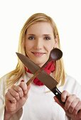 Female chef holding crossed kitchen knife and wooden spoon