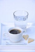 Espresso, heart-shaped biscuits and glass of water