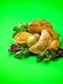 Assorted pies and pasties on salad leaves