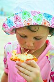 Child eating pizza on the beach