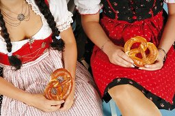 Two women in Bavarian traditional dress holding pretzels