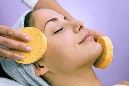 Young woman receiving facial massage, close-up