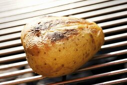 Barbecued potato on barbecue rack