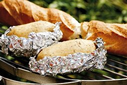 Baked potatoes and baguette on barbecue rack