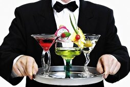 Bartender serving tray of different cocktails