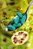 Spoonful of Noni capsules, fresh fruits, close-up