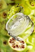 Noni cosmetics, fresh fruits in background, close-up