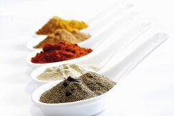 Various spices on spoons (ground pepper, paprika, curry powder)