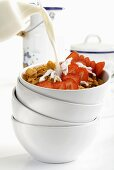 Pouring milk onto cornflakes and strawberries