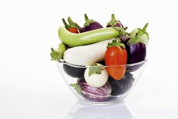Various types of aubergines in glass bowl