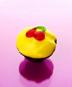 Muffin with yellow icing and jelly cherries
