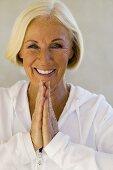 Senior woman meditating, smiling, close-up, portrait