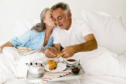 Mature couple sitting on bed with breakfast, women kissing man