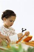 Girl (4-5) peeling carrot