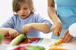 Son (4-7) and mother cutting vegetables, close-up