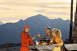 Peasant woman serving couple at alpine hut