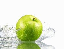 Green apple with splashing water
