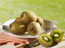 Several whole kiwi fruit on plate, halved fruit beside it