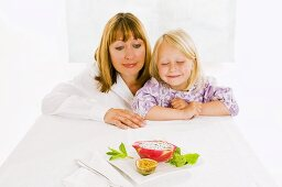 Mother and daughter sitting at table with plate of fruit