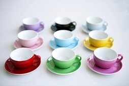 Coloured coffee cups and saucers in rows