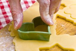 Cutting out a biscuit with a heart-shaped cutter