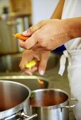 Chef in commercial kitchen peeling carrots