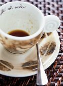 A coffee cup with a coffee bean pattern and leftover coffee