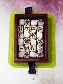 Zucker-Gruß im Kästchen (Würfelzucker mit Happy X-Mas Aufschrift aus Schoko-Glasur)