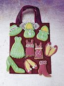 Rosa und grüne Modekekse in Form von Taschen, Kleidern und Schuhen
