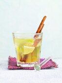 Hot Caipirinha with a cinnamon stick and limes