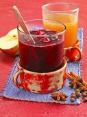 Baked apple wine punch and berry punch with star anise next to them